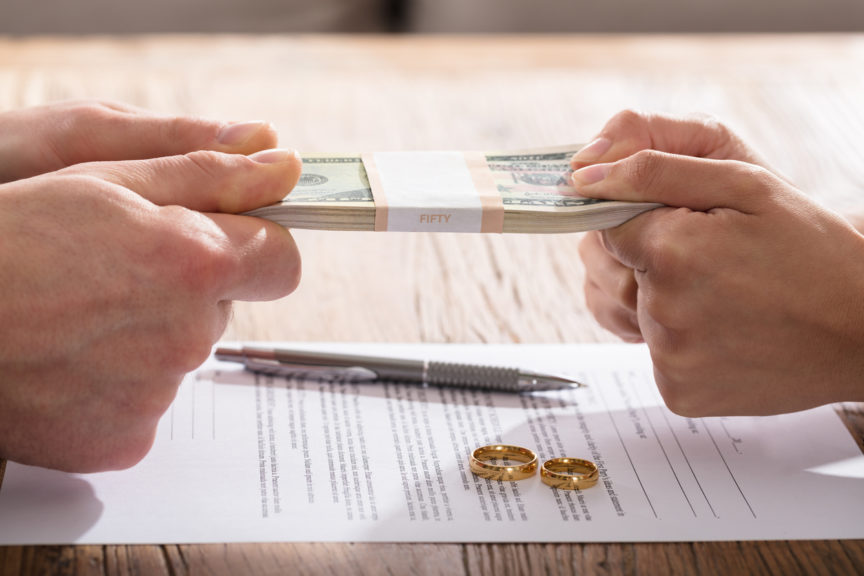 A couple holding a stack of cash and liquidating assets prior to divorce.